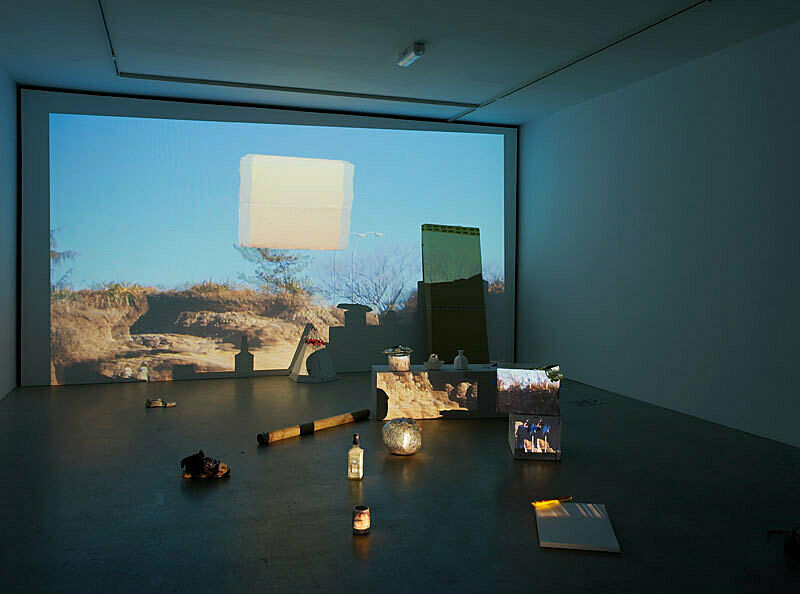 Installation view of Trish Baga Plymouth Rock exhibition; depicts a projection of rocks and trees with several objects including a teepee, clay pots, a shoe and a bottle in front of the projection.