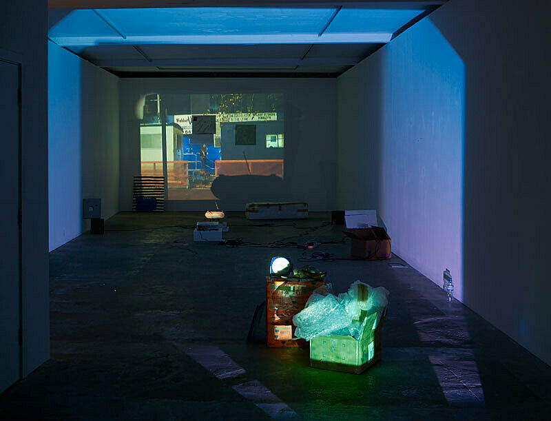 Installation view of Trisha Baga Plymouth Rock; depicts a projection of a person walking down stairs between buildings.
