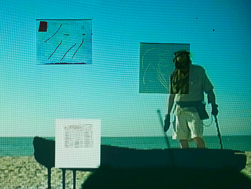 Close up of projection of a person walking on the beach with walking sticks and a silhouetted object before him.