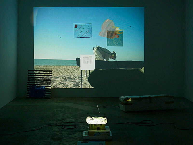 Installation view of Trisha Baga, Plymouth Rock; projection depicts an image of man in helmet on the beach with a silhouetted object before him.