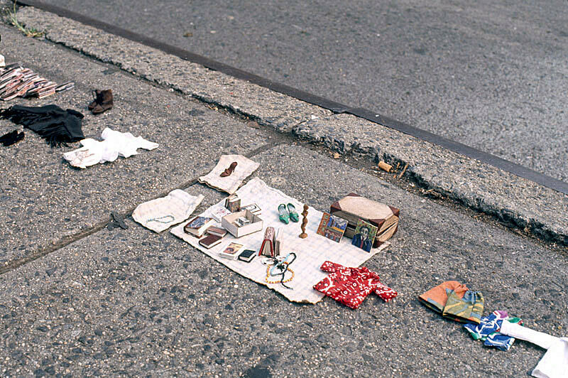 Installation view of Charles Ledray's workworkworkworkwork exhibition at New York's Astor place. Photograph depicts personal relics including shoes, clothing, a strand of beads, a jewelry box, books and photographs displayed on the sidewalk.