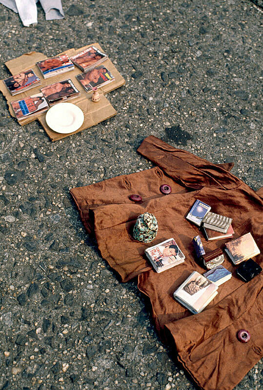 Installation view of Charles Ledray's workworkworkworkwork exhibition at New York's Astor Place. Photograph depicts a brown jacket with small books displayed on the sidewalk; beside the jacket is a piece of cardboard with a plate, a piece of pottery and magazines covers with images of nude men.