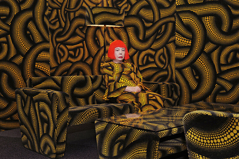 Woman sitting in room covered in pattern.