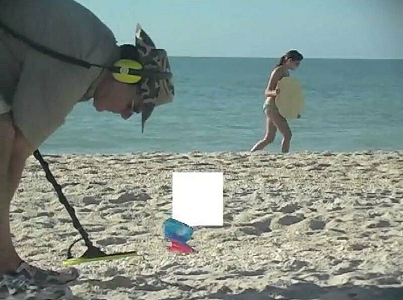 Man bending over a beach.