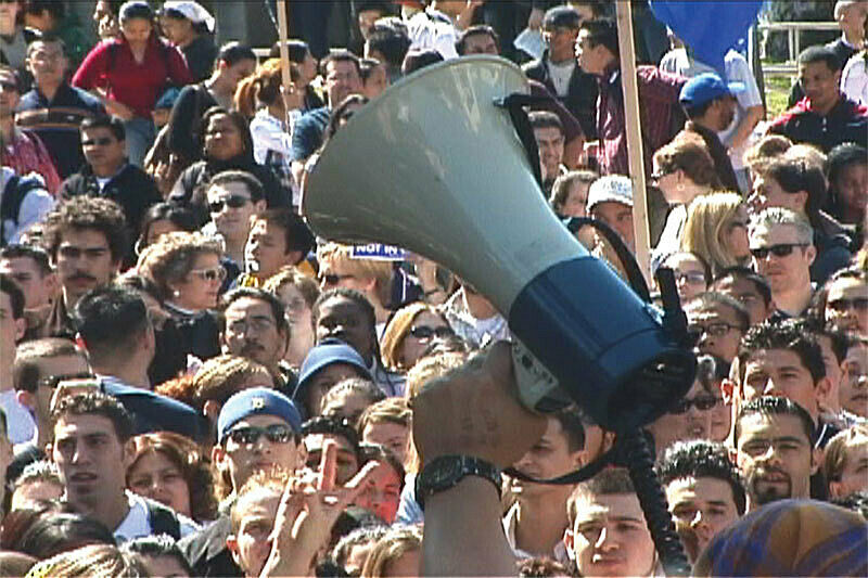 Film still of crowd and megaphone.