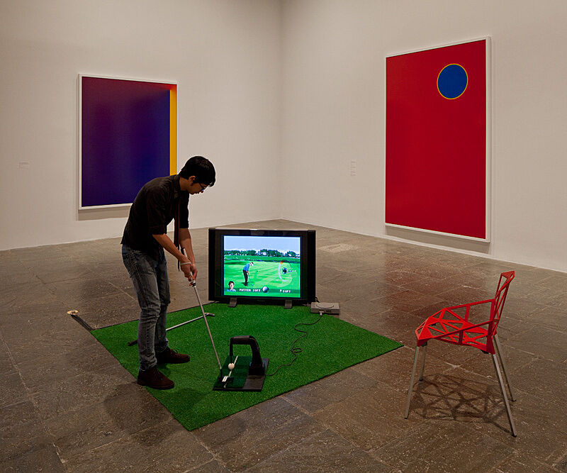 Man hitting a golf ball in a gallery.
