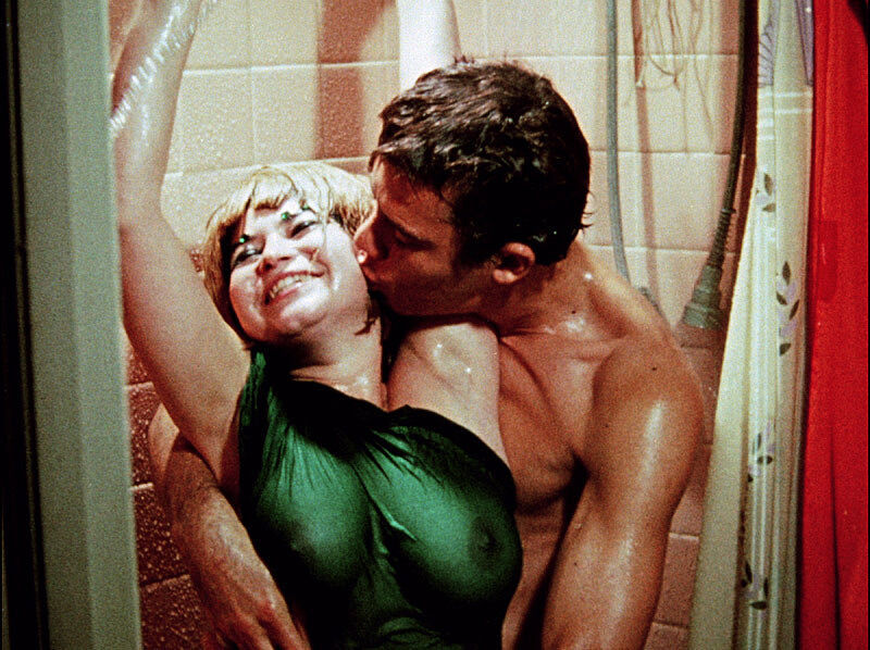 Woman in a dress with a man in the shower.