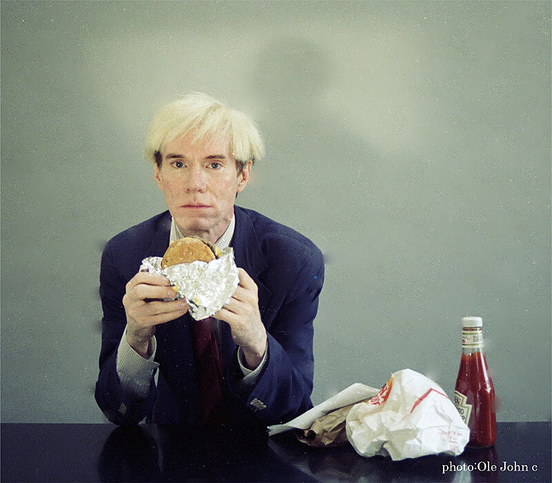 Andy Warhol eating a hamburger.