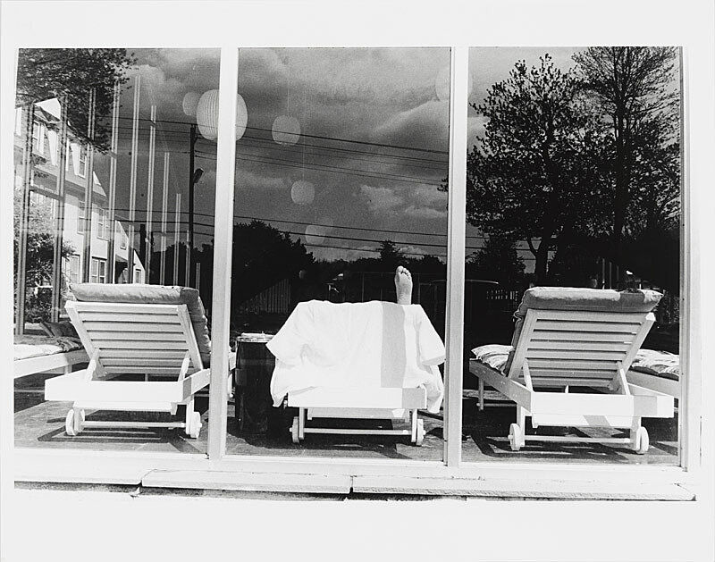 Black and white photograph chairs through a window.