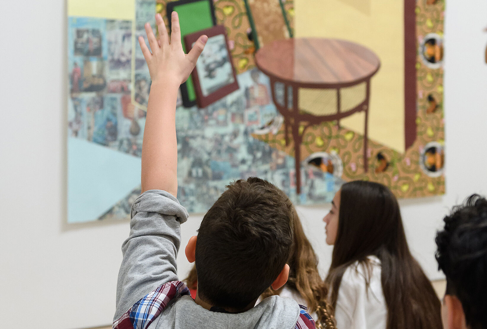 Child with raised hand in front of painting.