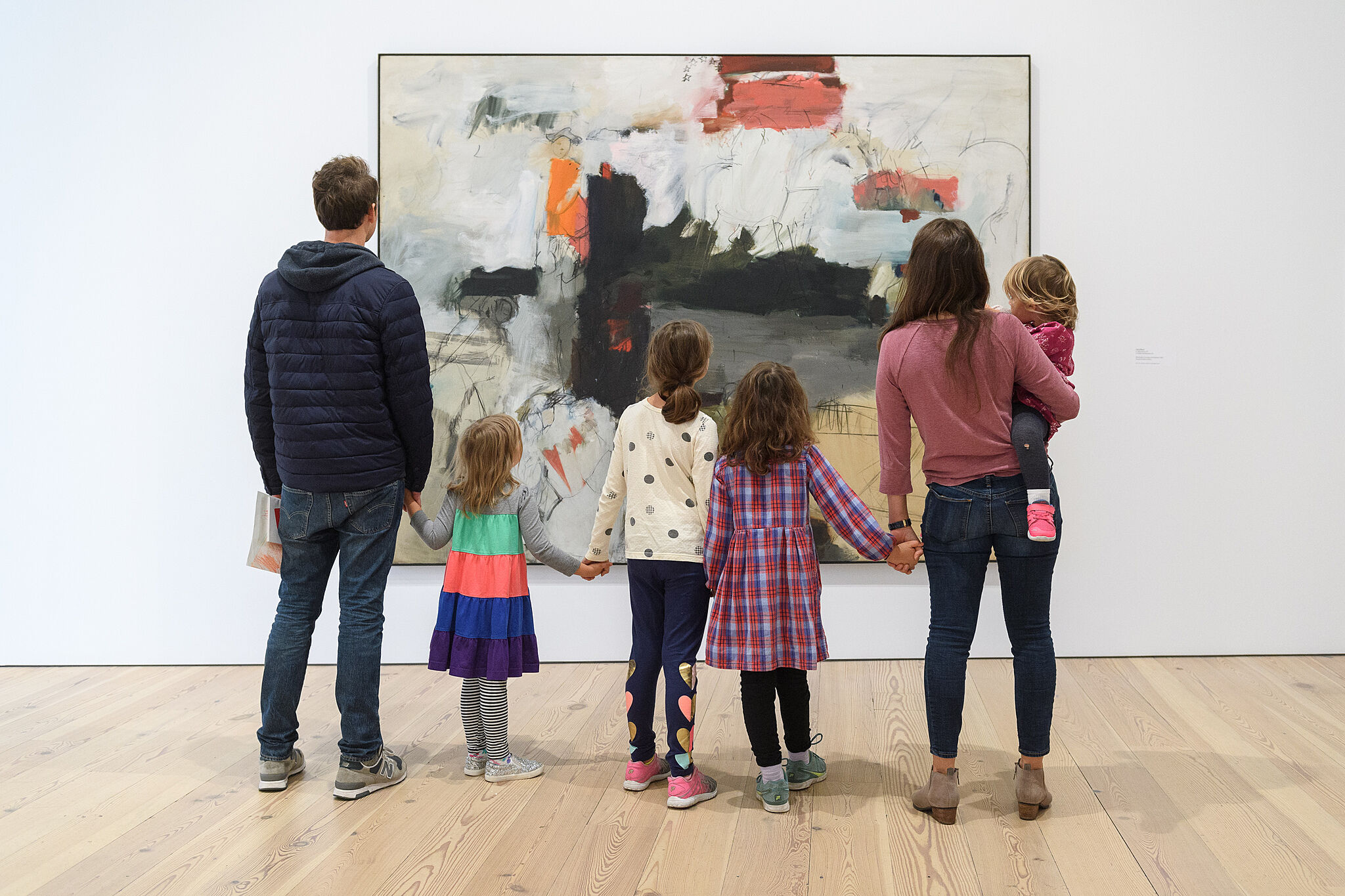 A family holding hands and looking at art.