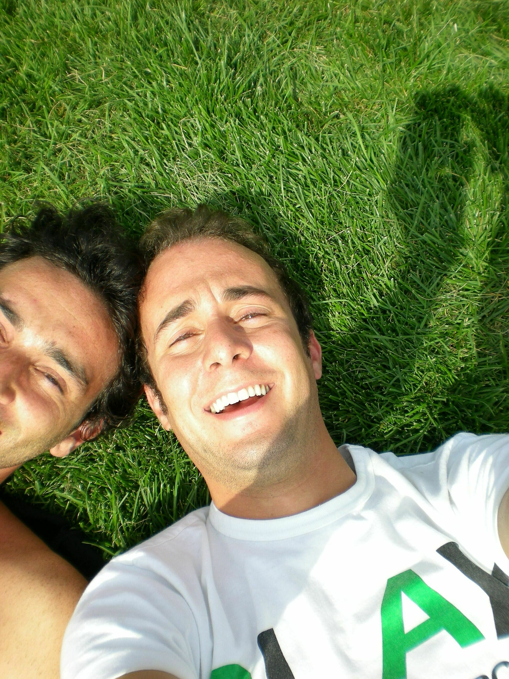 Photograph of a man and a friend taking a selfie in the grass.