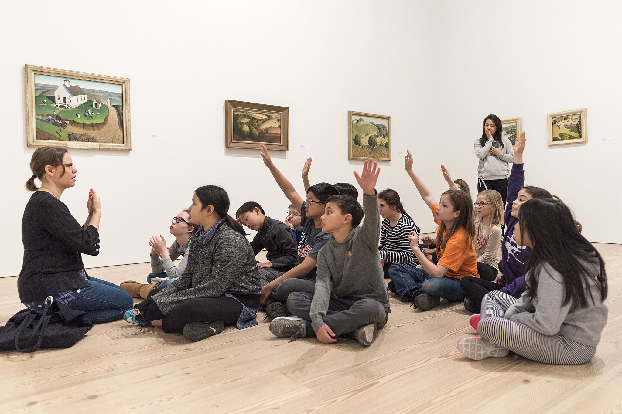 Children sitting on the floor in a gallery.