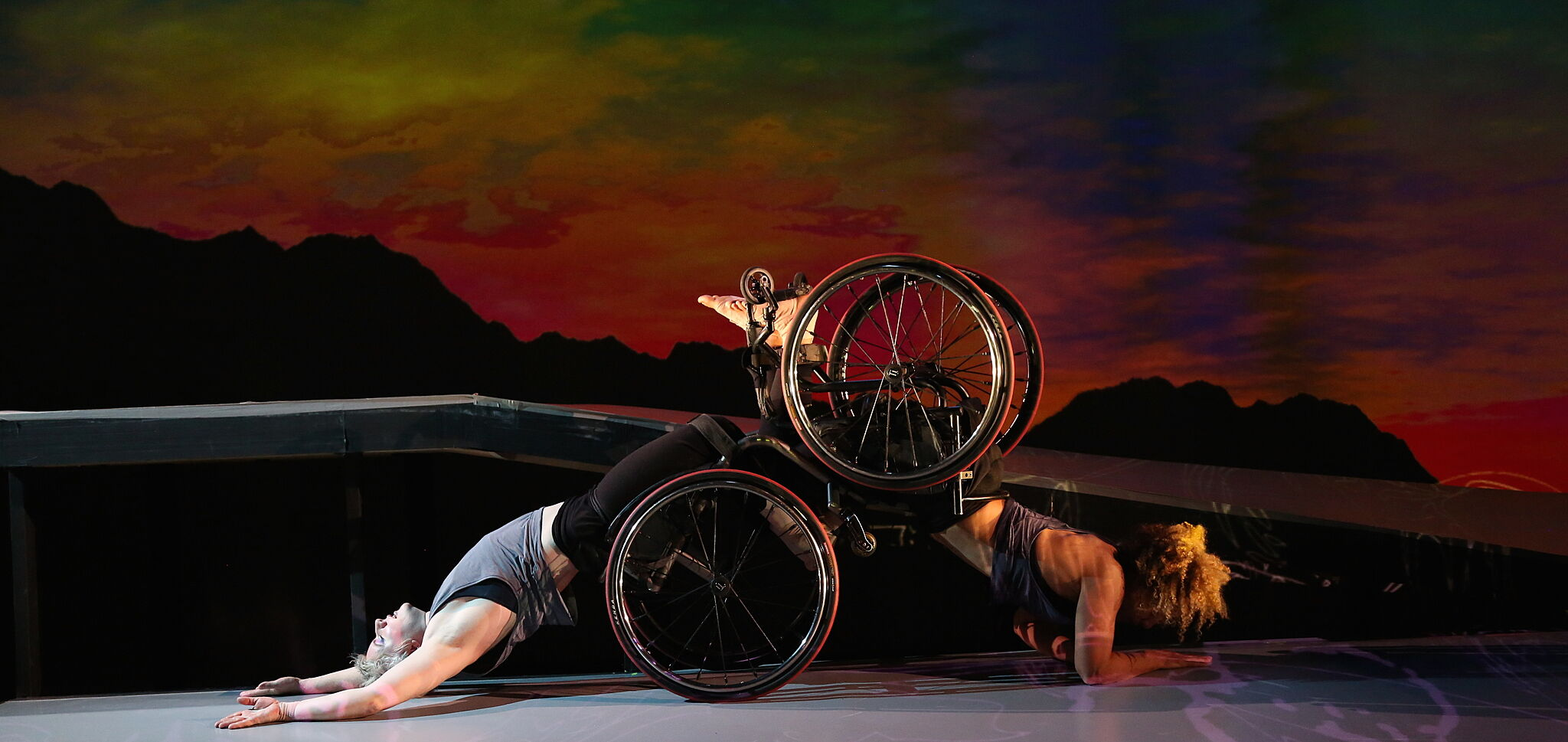 Two performers in wheelchairs doing a backbend.