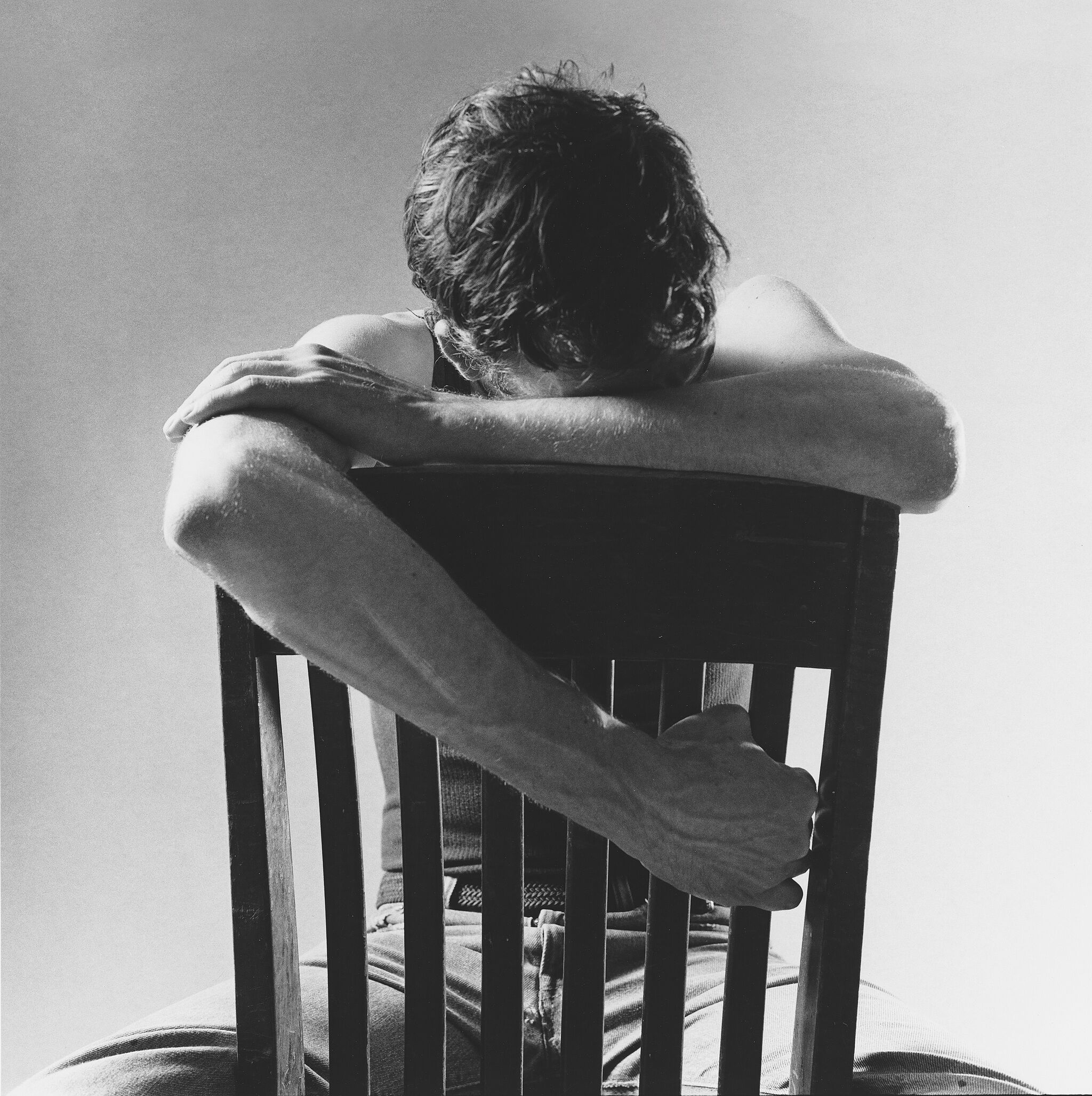 David Wojnarowicz sitting backwards on a chair.