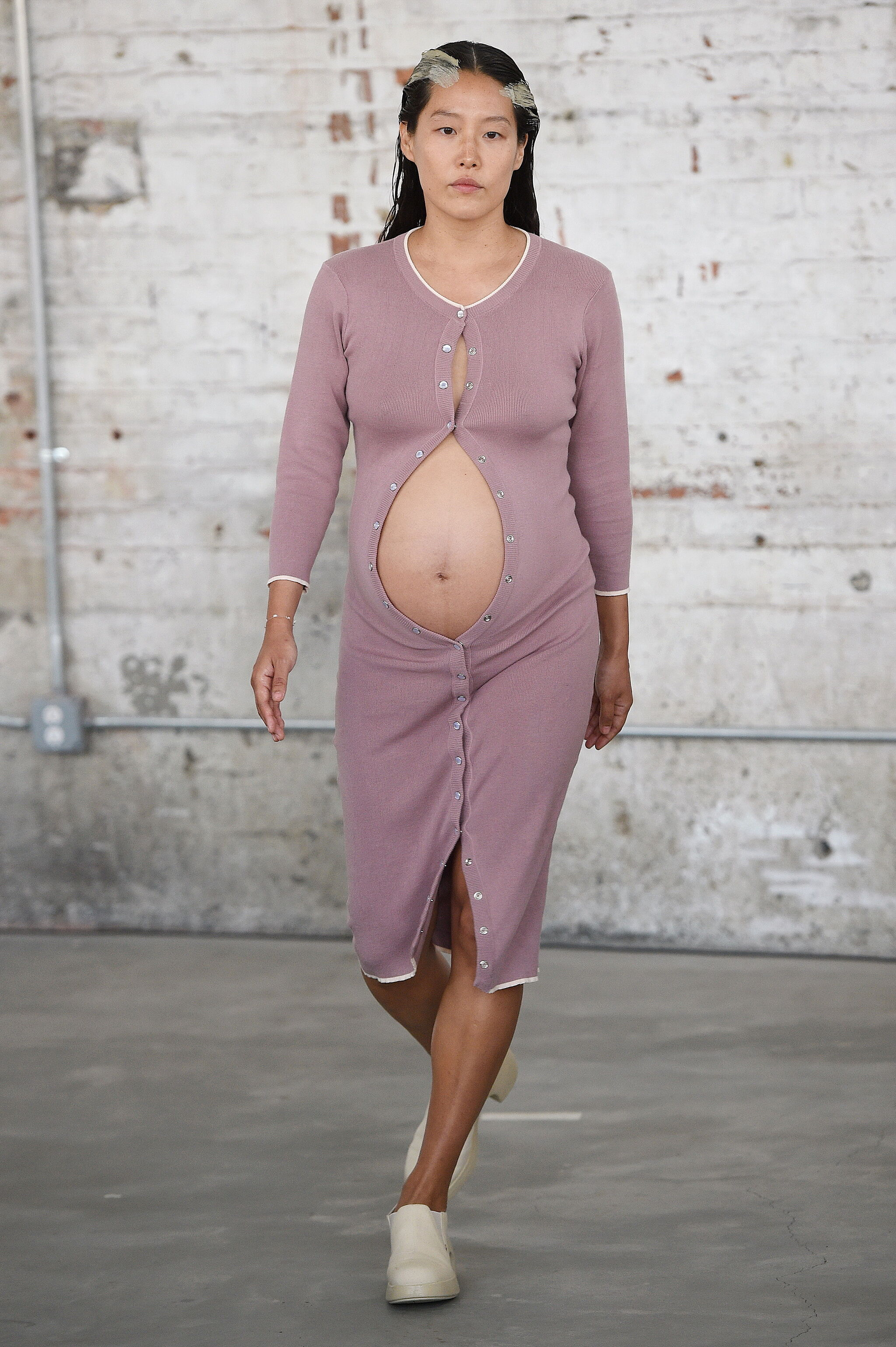 A pregnant woman in a dress opened at the stomach walking a runway.