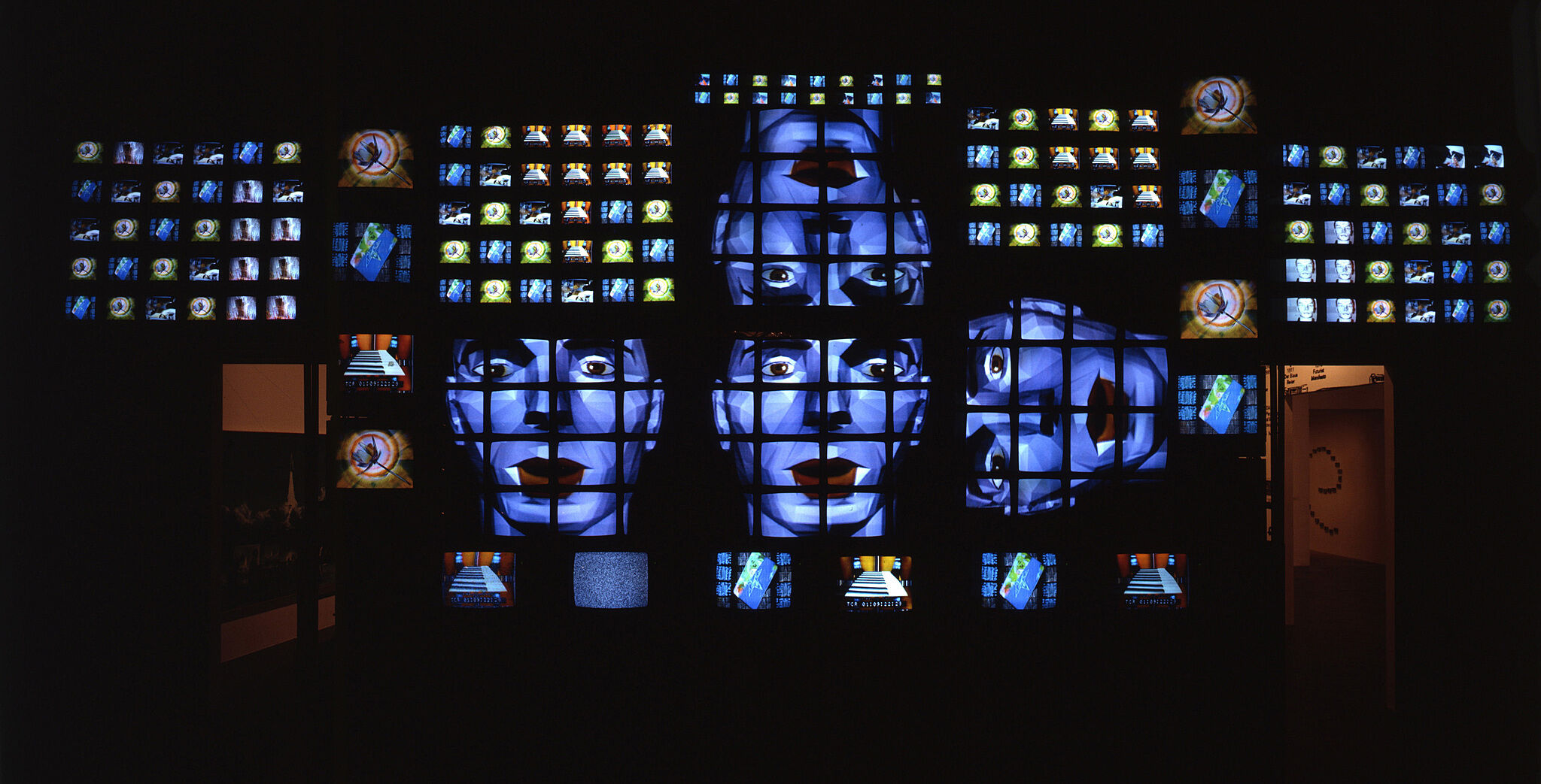 TV screens stacked on top of each other with faces.