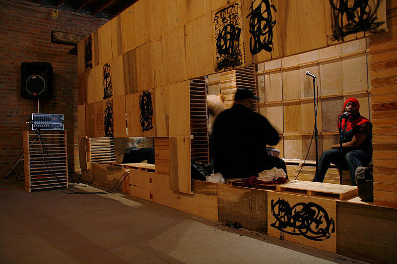 A man singing inside a wooden space.