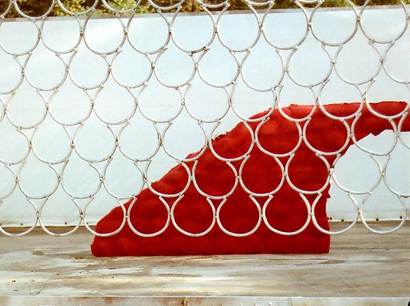 A piece of red flock behind an aluminium net.