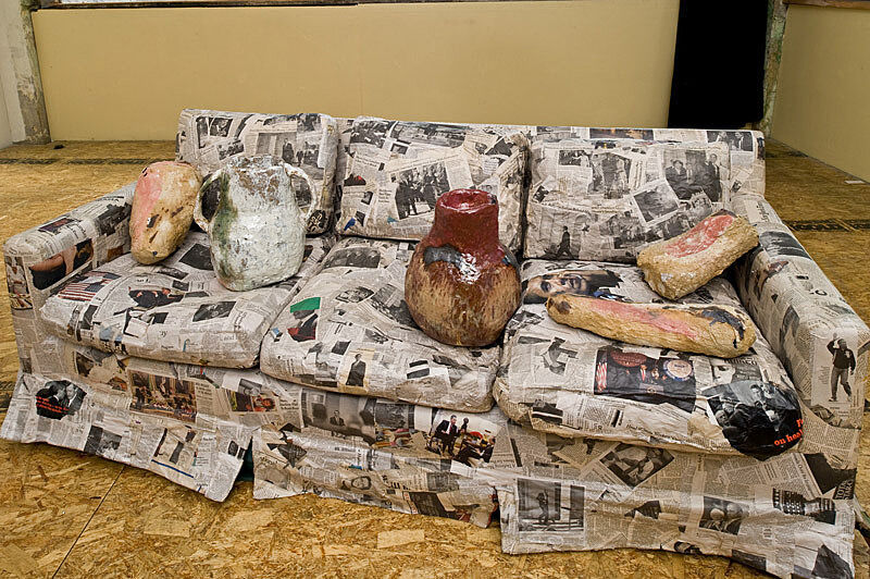 A couch wrapped with newspaper.