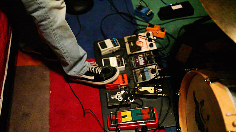 A person is playing different electronic music pedals.