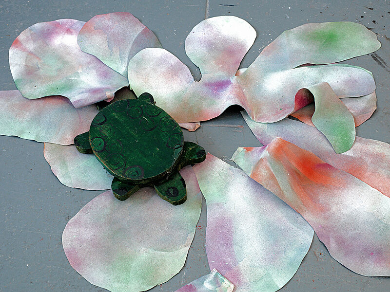 A wood turtle on paper flowers.
