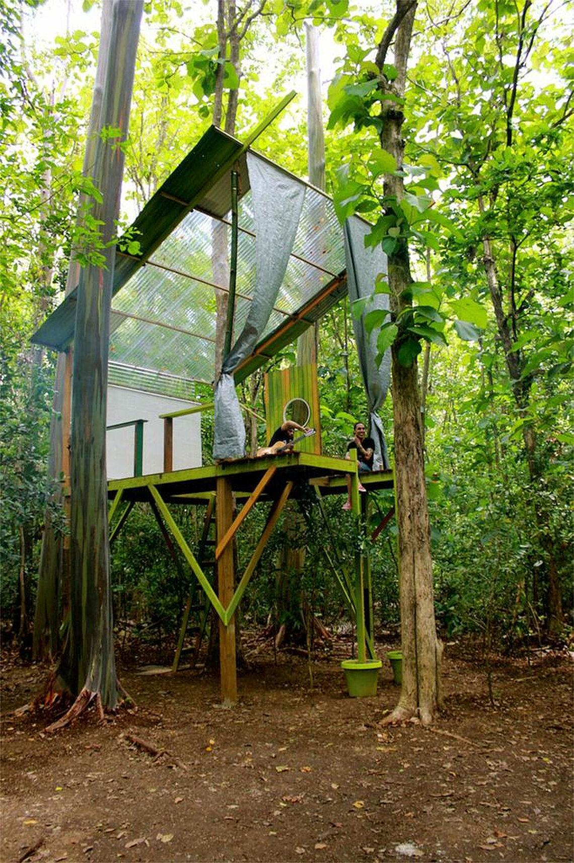 Two people sitting on a tree house.