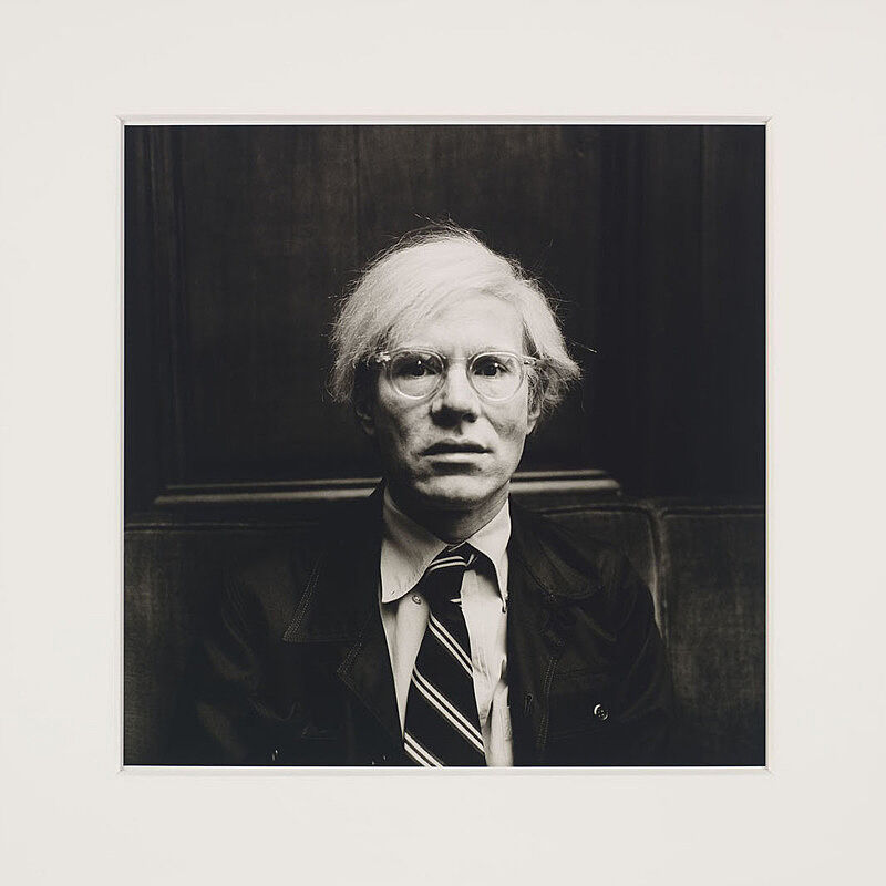 A black and white portrait of Andy Warhol