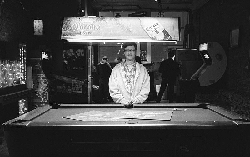 A black and white photograph of a man standing behind a pool table.