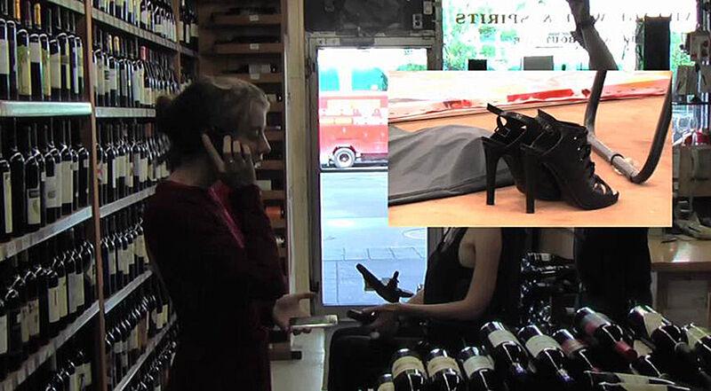 Still of two women in a wine shop.
