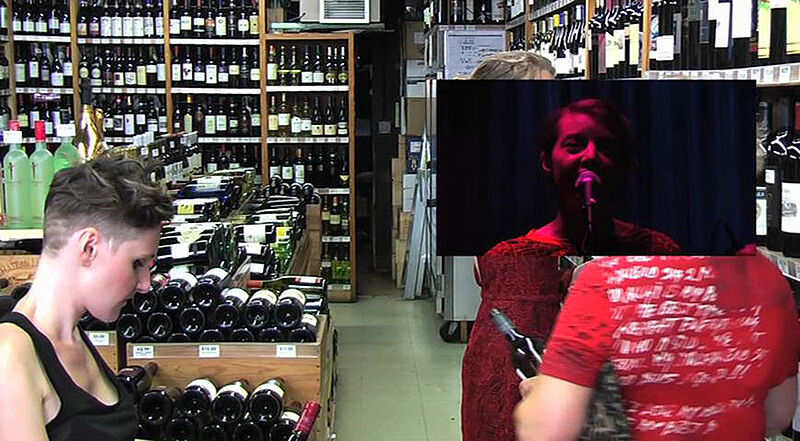 Still of three women in a wine shop.
