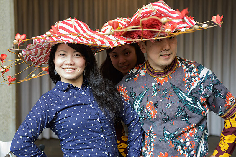 Three people wearing decorated hats.