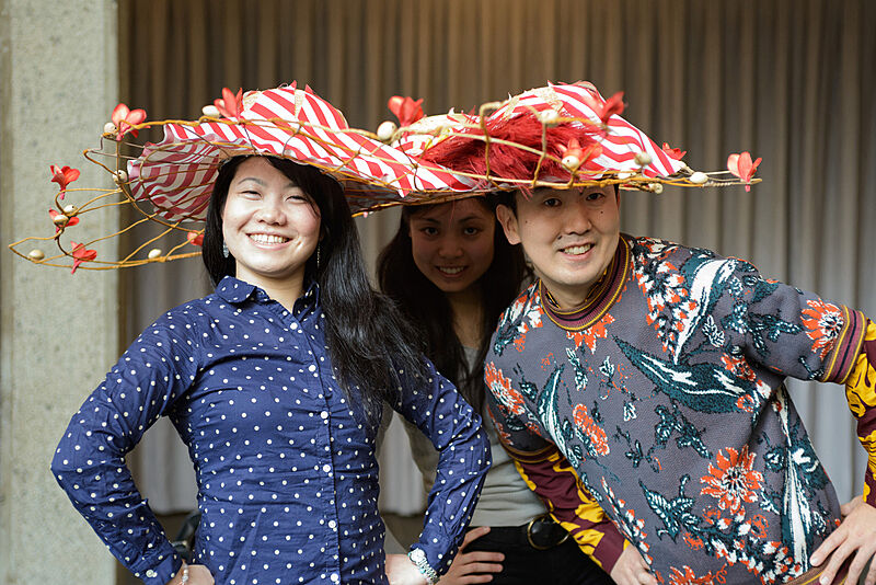 Three people wearing flower decorated hats.