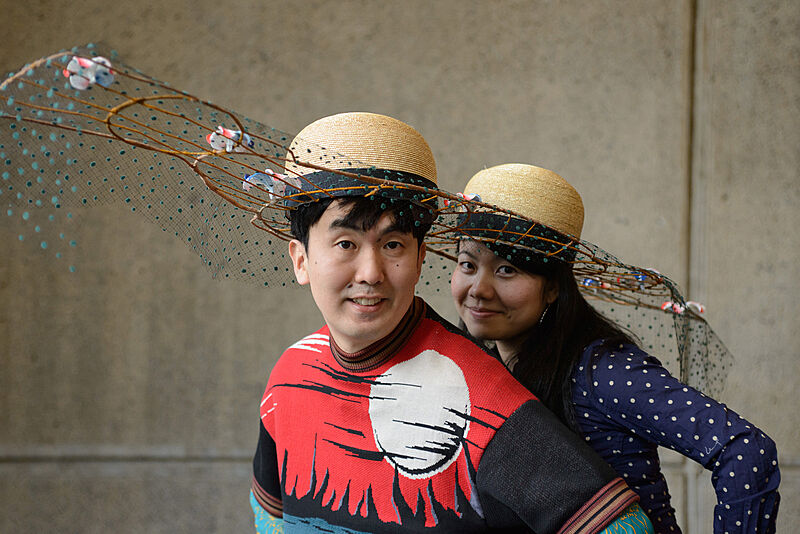 Two people wearing decorated hats.