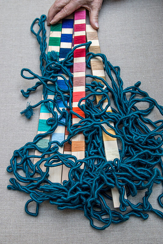 Threads of different colors on sticks.