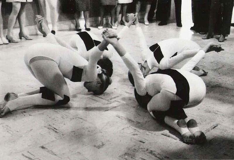 Four dancers dancing on the floor.