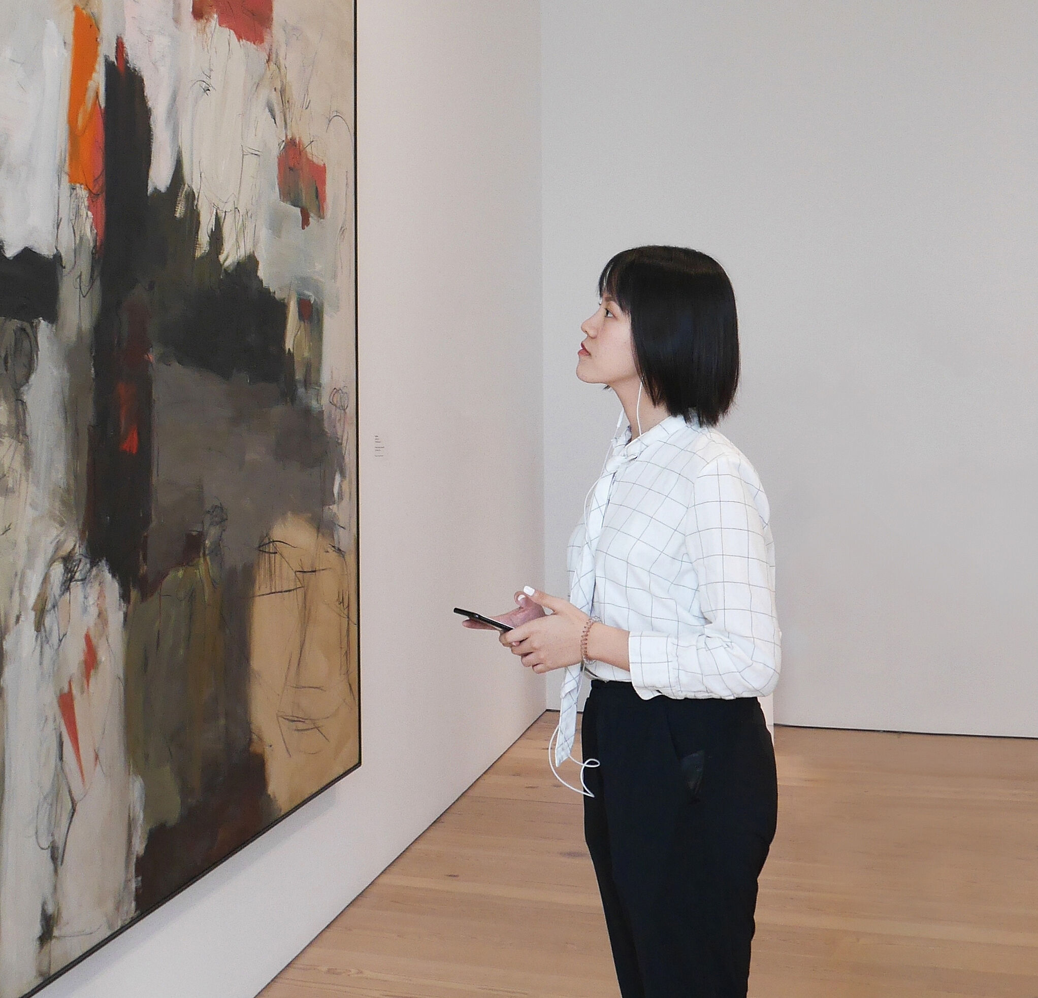 A visitor listens to the Whitney Mobile Guide on her phone.