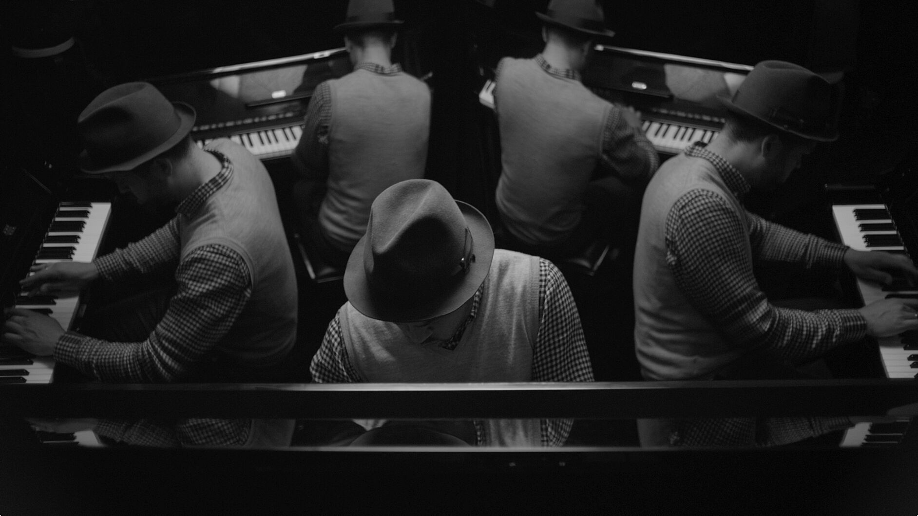 5 men in hats in a circle, facing away from each other and playing 5 different pianos