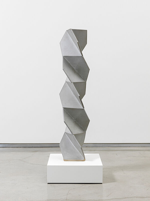 A tall grey and white ceramic artwork.