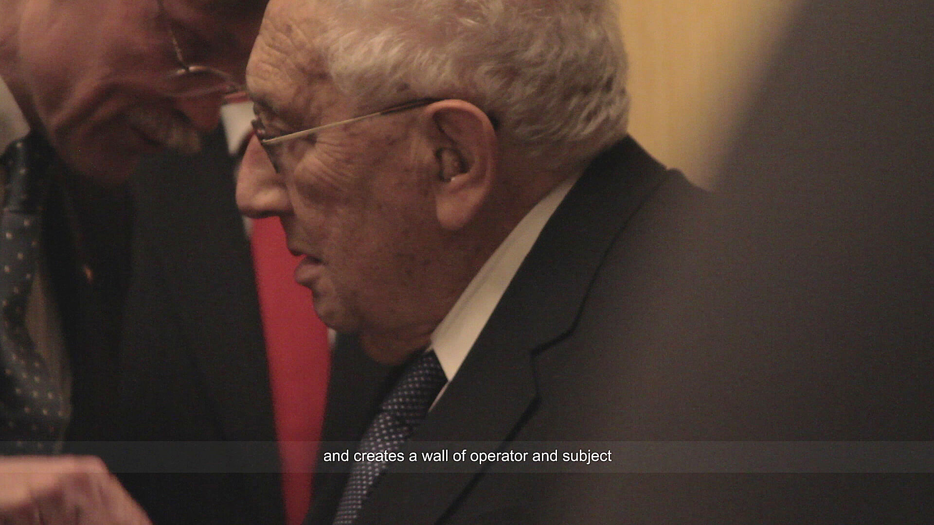 A still shot of a video of two old men in suit talking.
