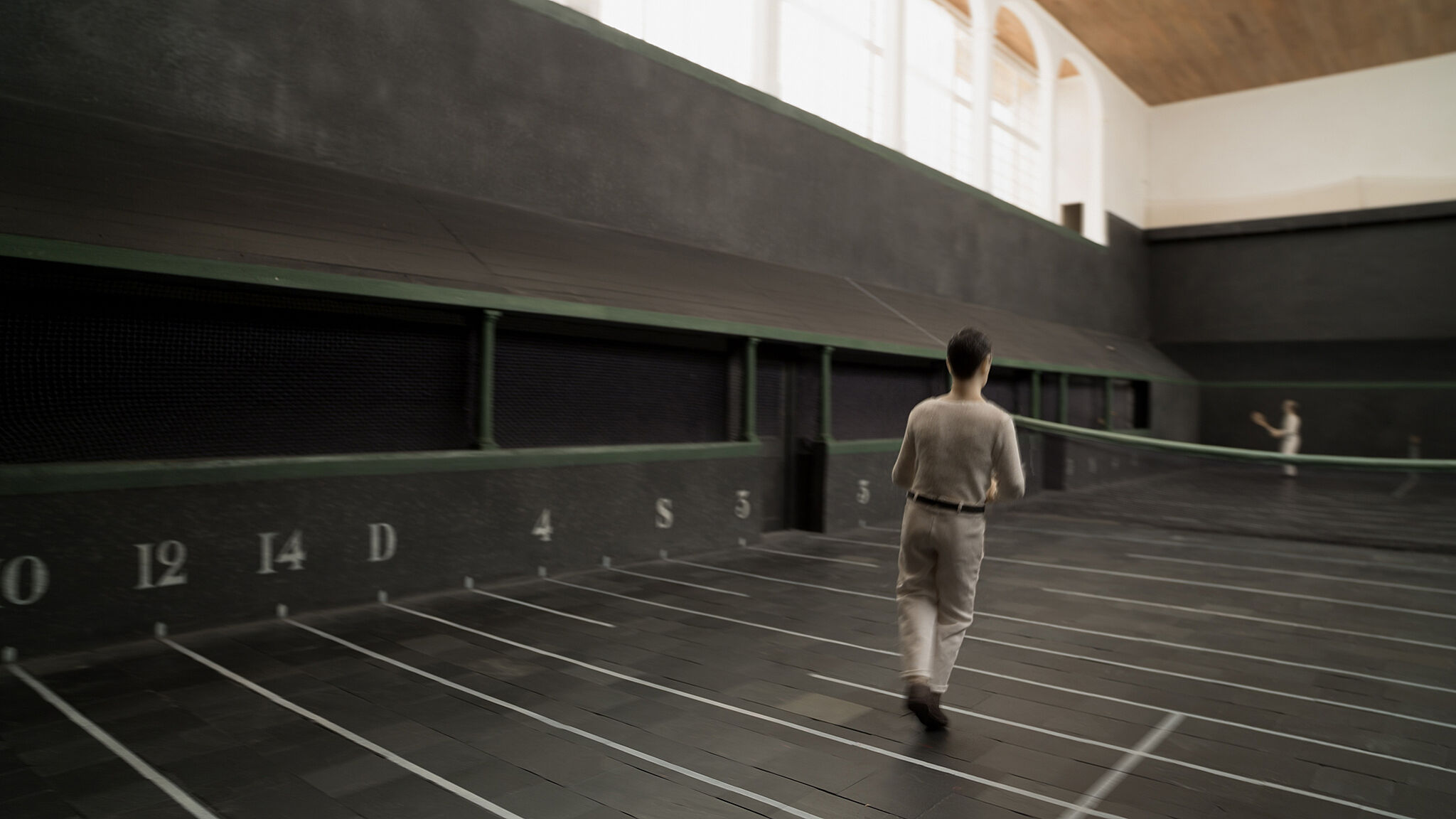 A still from an animation of a man playing tennis.