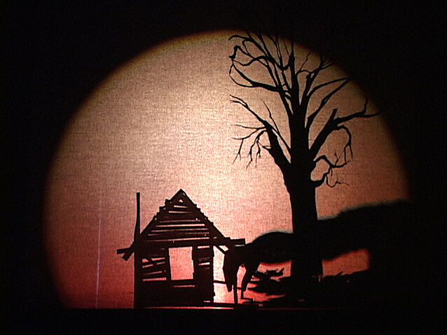 Shadow play of a cutting of a tree and a house.