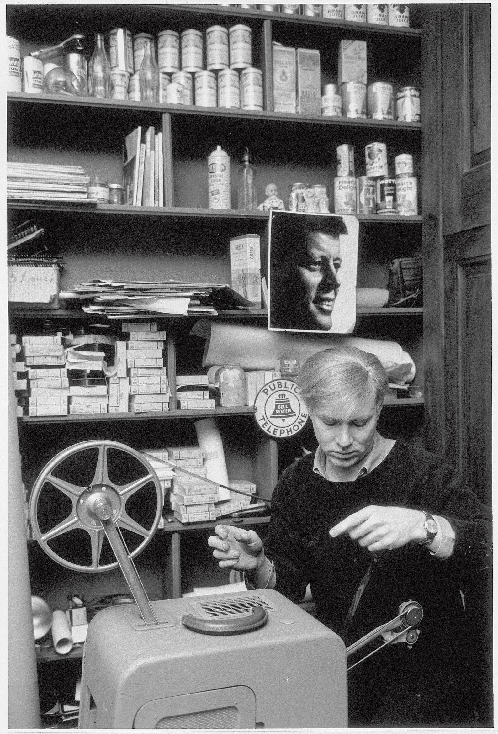 Black and white photograph of Andy Warhol examining a film strip