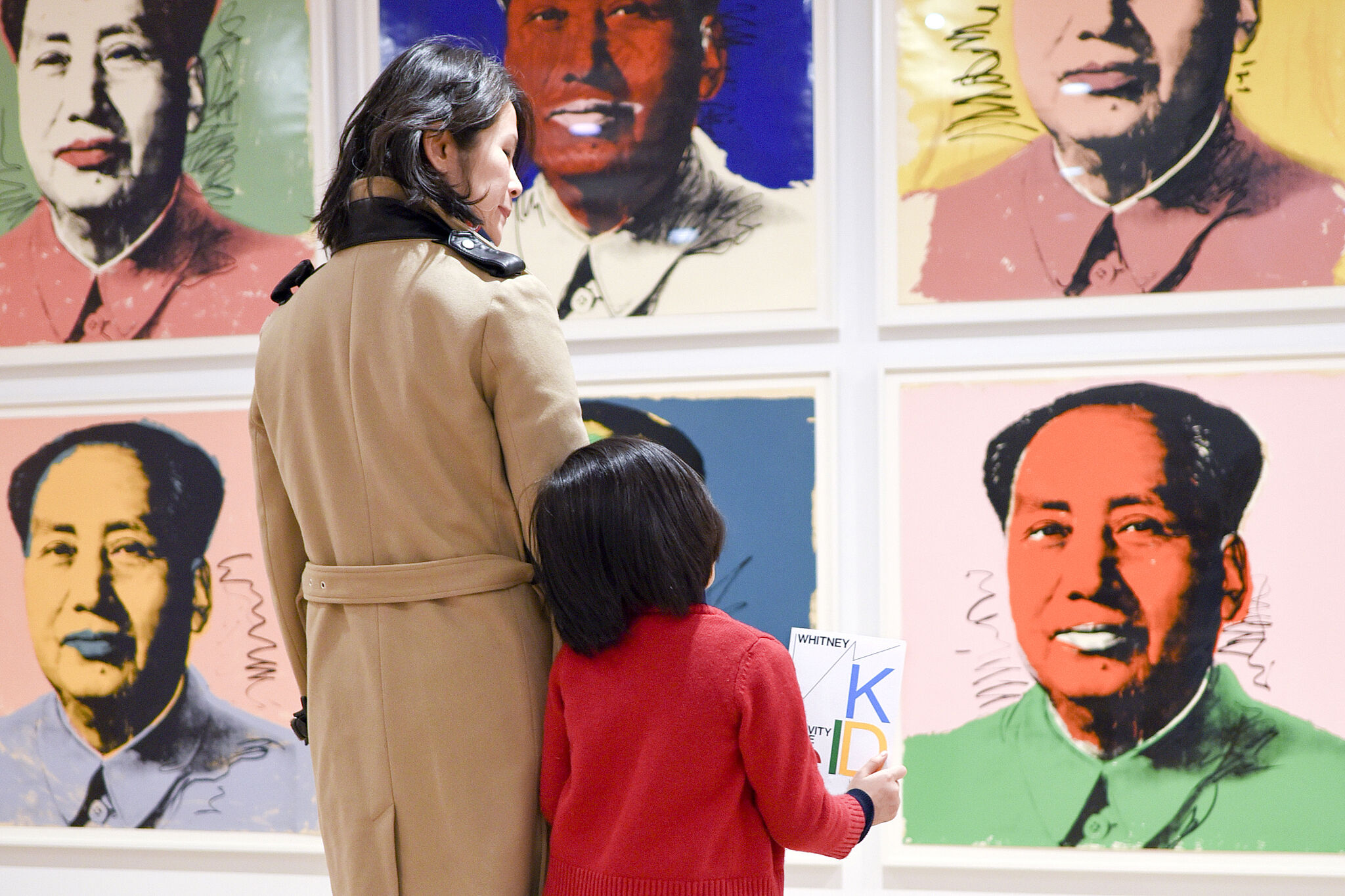 A parent and child look at Warhol's Mao paintings