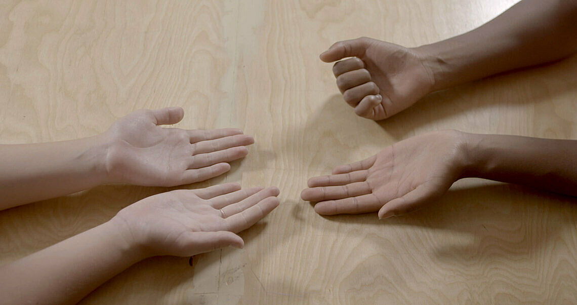 Three hands are open on a wooden surface, a fourth hand is in a fist
