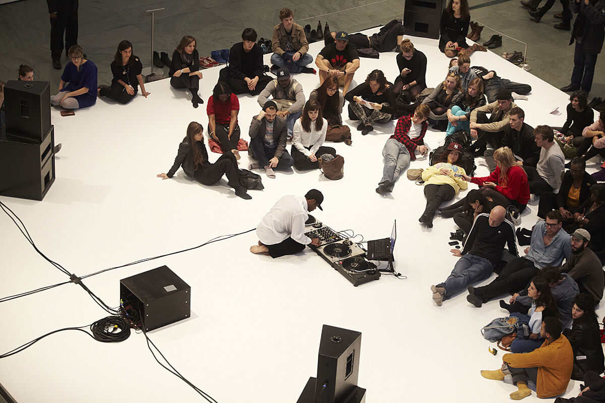 People sitting on a white floor as part of a performance.