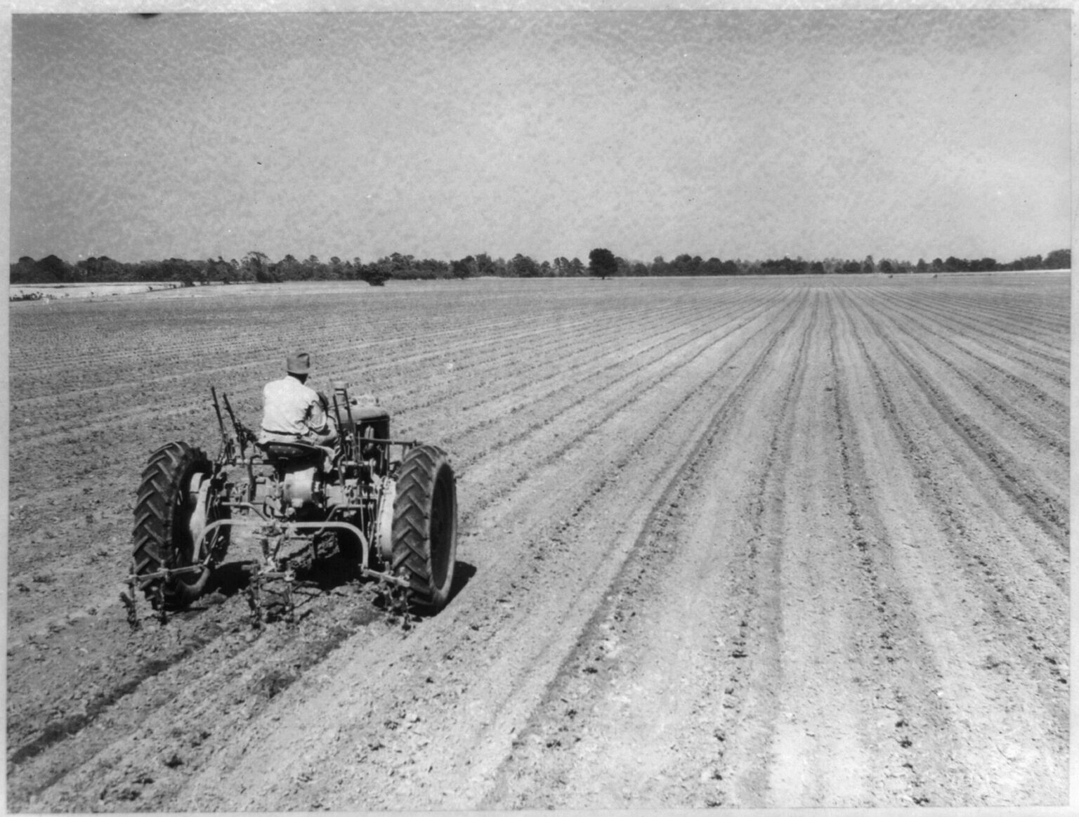 A black and white photograph of a tractor in a field.