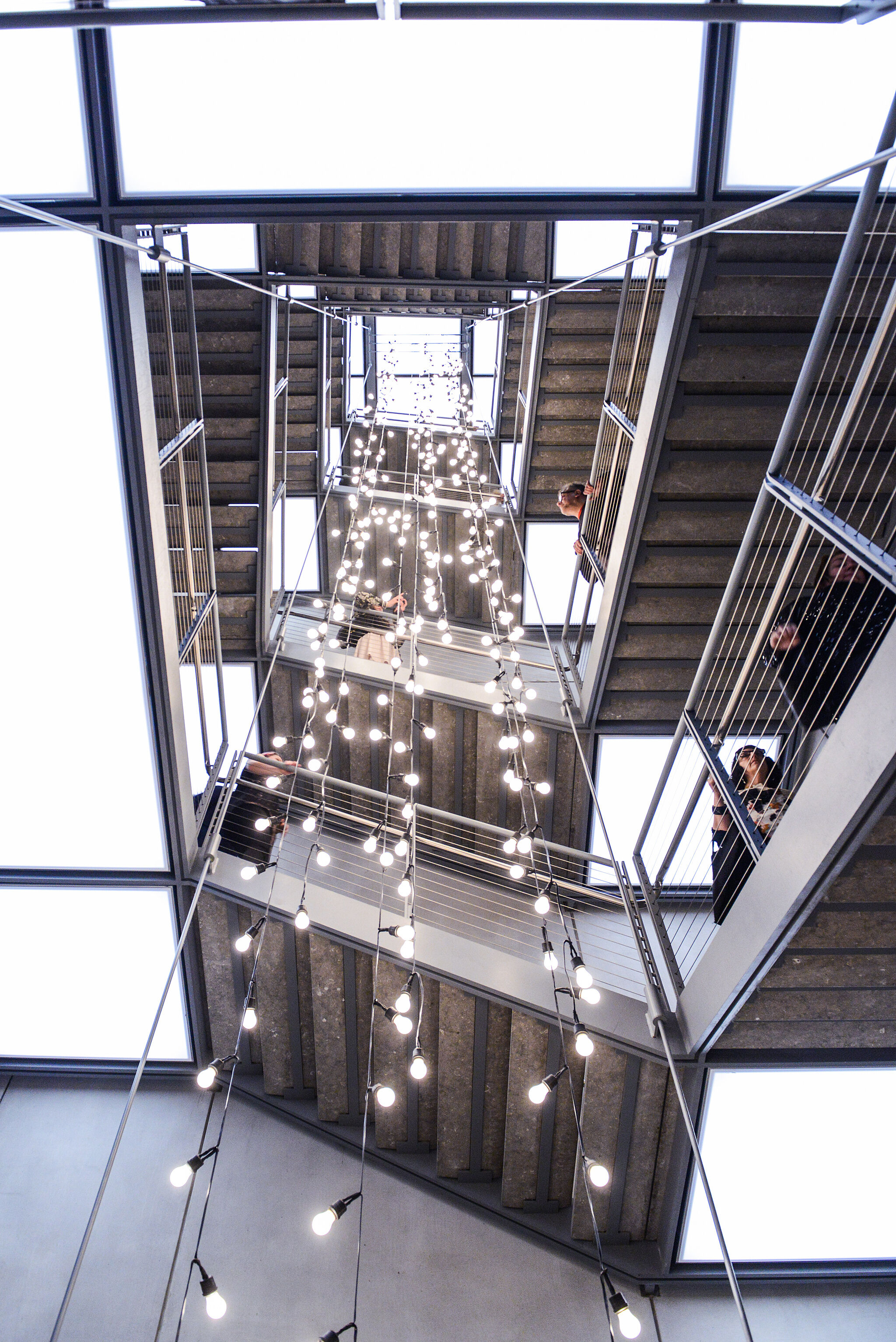 An installation in the Whitney's stairwell featuring white string lights.