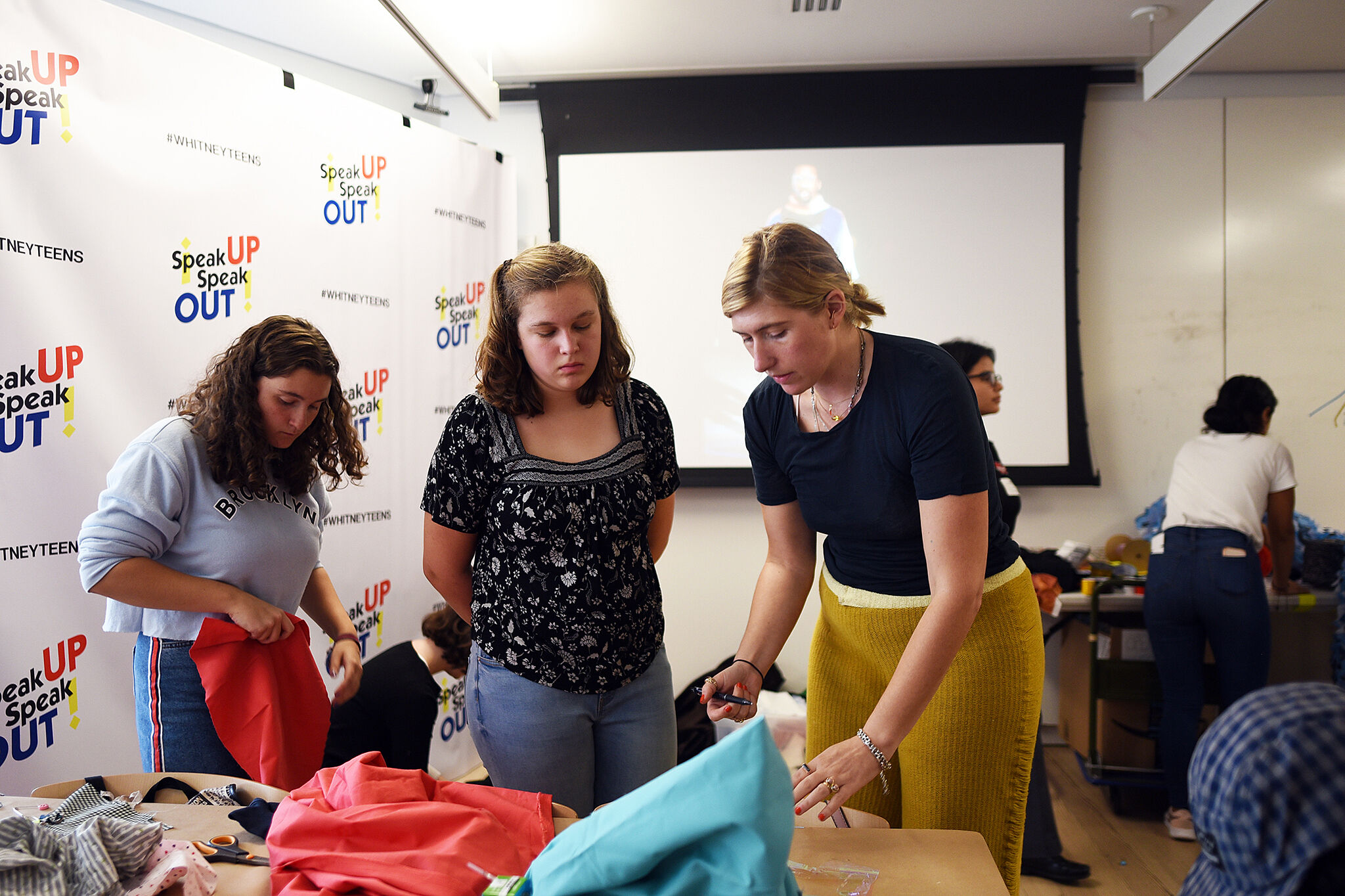 An instructor and two teen artists stand at a table and work with fabric