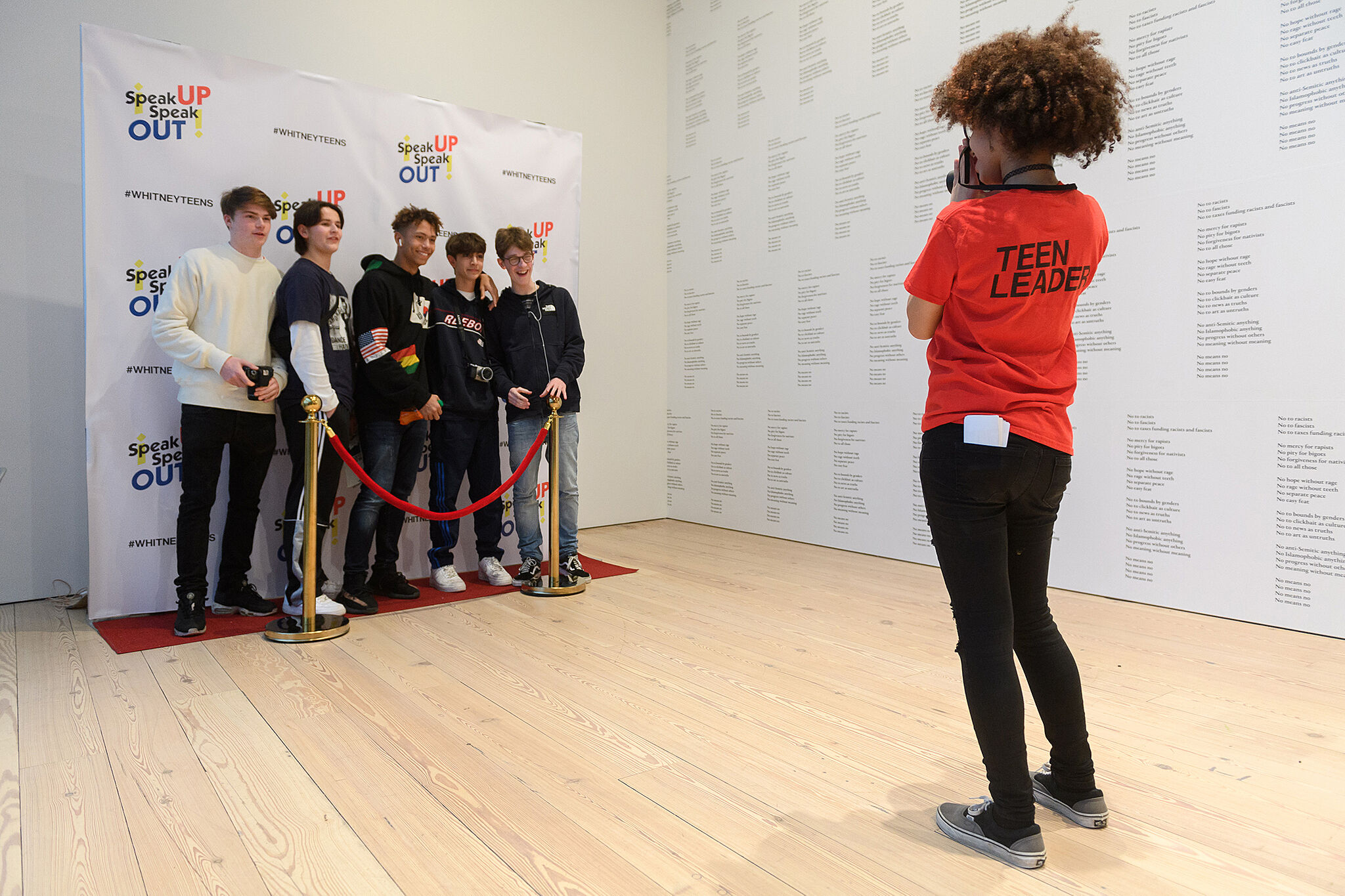 "Five teens stand behind a red carpet rope, and pose for a photographer wearing a shirt labeled ""teen leader"""